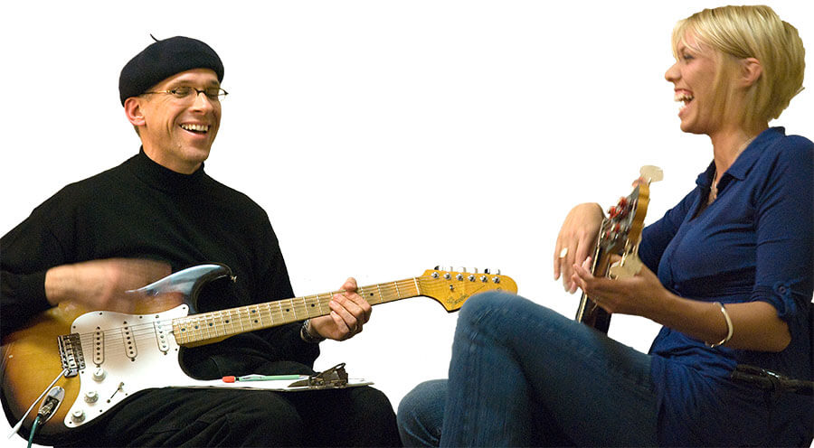 Robert Jones laughing with guitar lessons student