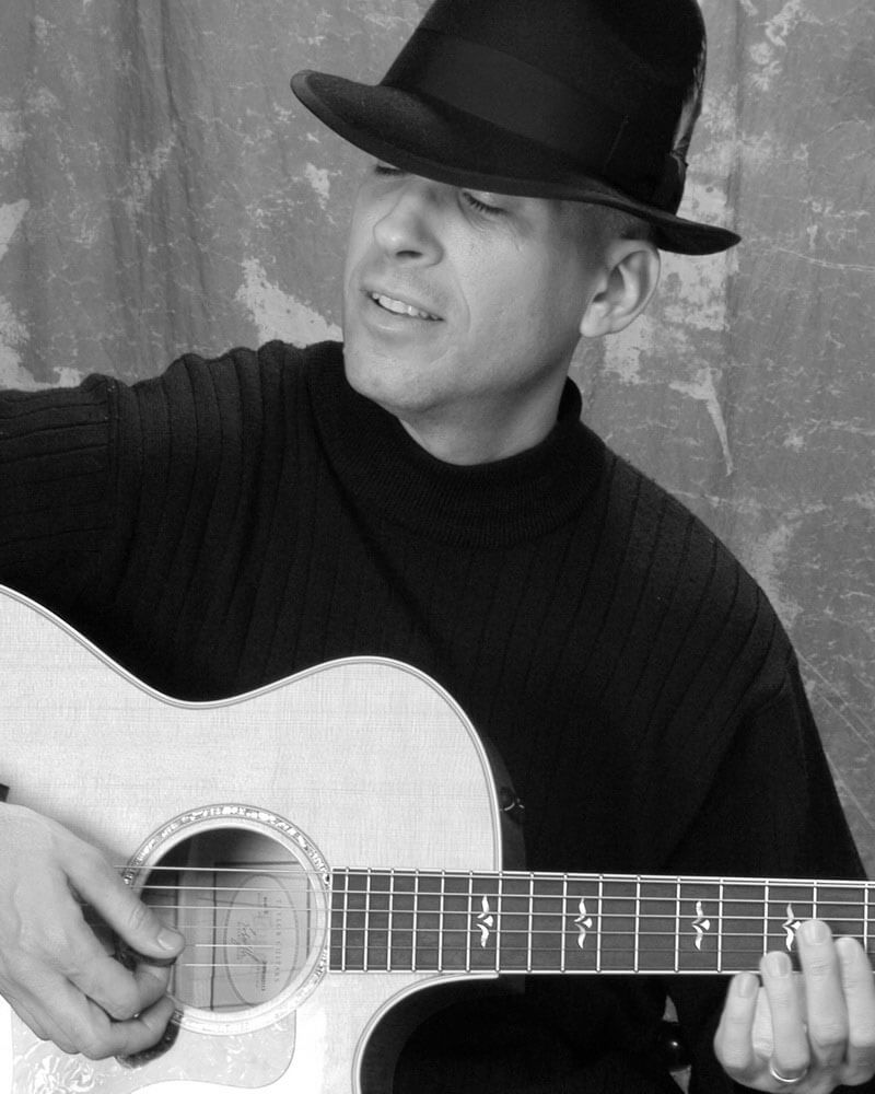 Robert Jones playing acoustic guitar black and white image